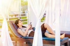 Muchacha adolescente Biracial que se relaja debajo de sombra del sol usando el teléfono móvil Imágenes de archivo libres de regalías