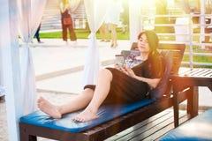 Muchacha adolescente Biracial que se relaja debajo de sombra del sol usando el teléfono móvil Imagen de archivo