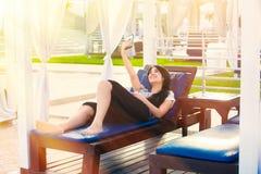Muchacha adolescente Biracial que se relaja debajo de sombra del sol usando el teléfono móvil Imagenes de archivo