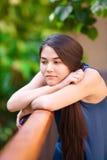 Muchacha adolescente Biracial que sostiene el teléfono móvil, inclinándose en la verja, thinki Fotografía de archivo