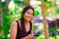 Muchacha adolescente Biracial que usa el teléfono móvil en el ajuste tropical Fotografía de archivo libre de regalías