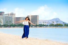 Muchacha adolescente biracial sonriente que camina a lo largo de la playa en Honolulu, Hawa Imágenes de archivo libres de regalías