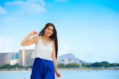 Muchacha adolescente biracial sonriente que camina a lo largo de la playa en Honolulu, Hawa Fotos de archivo