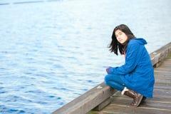Muchacha adolescente biracial triste, sola en el embarcadero de madera por el agua Fotos de archivo