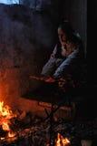 Muchacha adolescente calentada por el fuego en una casa abandonada Imagen de archivo libre de regalías