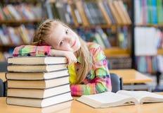 Muchacha adolescente cansada en biblioteca Foto de archivo