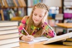 Muchacha adolescente cansada que estudia en la biblioteca Imagen de archivo libre de regalías