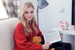 Muchacha adolescente caucásica feliz que descansa sobre el sofá en la sala de estar mientras que libro de lectura Foto de archivo