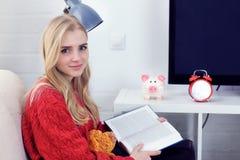 Muchacha adolescente caucásica feliz que descansa sobre el sofá en la sala de estar mientras que libro de lectura Imagen de archivo