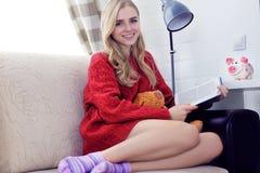 Muchacha adolescente caucásica feliz que descansa sobre el sofá en la sala de estar mientras que libro de lectura Foto de archivo libre de regalías