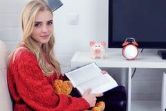 Muchacha adolescente caucásica feliz que descansa sobre el sofá en la sala de estar mientras que libro de lectura Imagenes de archivo