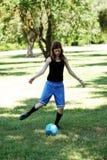 Muchacha adolescente caucásica flaca que golpea el balón de fútbol con el pie azul Fotos de archivo libres de regalías