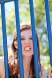 Muchacha adolescente caucásica joven que grune a través de barras Fotografía de archivo