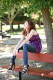 Muchacha adolescente caucásica joven que se sienta en banco de parque Foto de archivo libre de regalías