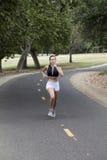 Muchacha adolescente caucásica que corre en la trayectoria de la bici en parque Imagen de archivo