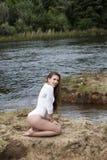 Muchacha adolescente caucásica que se sienta en la isla del fango en el río Foto de archivo libre de regalías