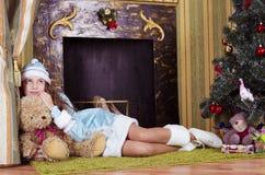 Muchacha adolescente cerca de la chimenea con el oso de peluche Foto de archivo