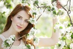 Muchacha adolescente cerca del árbol del flor Fotografía de archivo