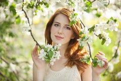 Muchacha adolescente cerca del árbol del flor Imagenes de archivo