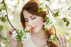 Muchacha adolescente cerca del árbol del flor Imágenes de archivo libres de regalías