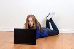 Muchacha adolescente chocada usando el ordenador portátil Fotos de archivo