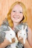 Muchacha adolescente con dos conejos Imágenes de archivo libres de regalías