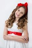 Muchacha adolescente con el arco rojo en la cabeza Fotos de archivo