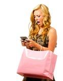 Muchacha adolescente con el bolso de compras texting Imagenes de archivo