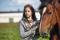 Muchacha adolescente con el caballo marrón Fotografía de archivo libre de regalías
