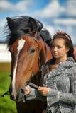 Muchacha adolescente con el caballo marrón Imagen de archivo libre de regalías