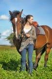 Muchacha adolescente con el caballo marrón Imagenes de archivo