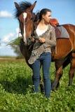 Muchacha adolescente con el caballo marrón Fotos de archivo libres de regalías