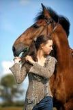 Muchacha adolescente con el caballo marrón Fotografía de archivo