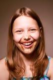Muchacha adolescente con el chocolate en su cara Fotos de archivo libres de regalías