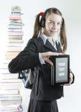 Muchacha adolescente con el ebook y la pila de libros impresos Imagen de archivo libre de regalías