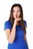 Muchacha adolescente con el finger en sus labios. Foto de archivo libre de regalías