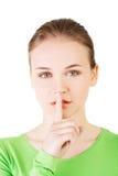 Muchacha adolescente con el finger en sus labios. Imagenes de archivo