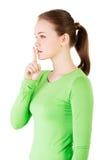 Muchacha adolescente con el finger en sus labios. Imagen de archivo libre de regalías