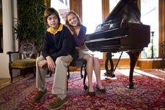 Muchacha adolescente con el hermano por el piano Fotos de archivo