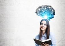Muchacha adolescente con el holograma del libro negro y del cerebro Fotografía de archivo