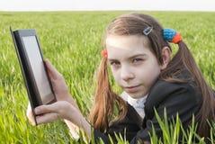 Muchacha adolescente con el libro electrónico Fotografía de archivo libre de regalías