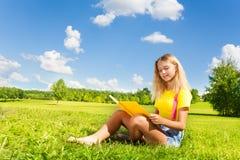 Muchacha adolescente con el libro en el parque Foto de archivo
