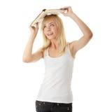 Muchacha adolescente con el libro sobre su cabeza Foto de archivo