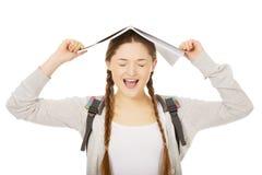 Muchacha adolescente con el libro sobre su cabeza Fotografía de archivo libre de regalías