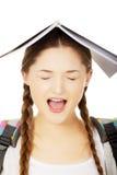 Muchacha adolescente con el libro sobre su cabeza Imagenes de archivo