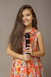 Muchacha adolescente con el micrófono negro a disposición imagen de archivo libre de regalías