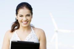 Muchacha adolescente con el ordenador de la tableta al lado de la turbina de viento. Imagenes de archivo