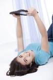 Muchacha adolescente con el ordenador de la tablilla en suelo Imagen de archivo libre de regalías