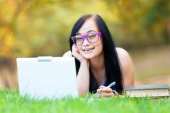 Muchacha adolescente con el ordenador portátil Imágenes de archivo libres de regalías