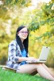 Muchacha adolescente con el ordenador portátil Foto de archivo libre de regalías
